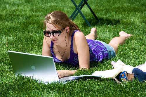 How to Earn Online? Girl using apple laptop in grasses.