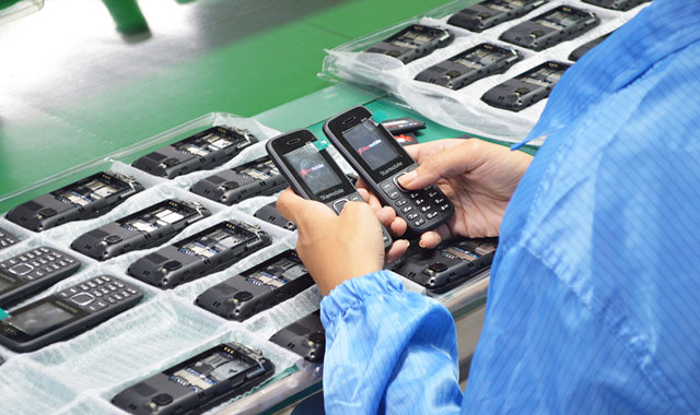 A worker inspects the Starmobile phones assembled in the company's facility.