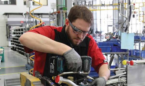 A worker wears a Google Glass Enterprise Edition while assembling machine parts.