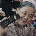 Lola Dominga shows the Cloudfone Lite Senior Flip she received during Cloudfone's CSR Give-Back Project.