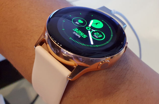 The Samsung Galaxy Watch Active with rose pink watch and light pink strap.